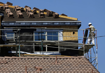 A worker walks on scaffolding at the construction site of a new home in Carlsbad