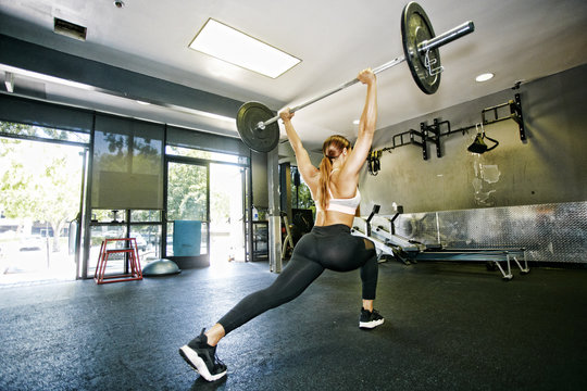 Mixed Race woman lifting barbell in gymnasium