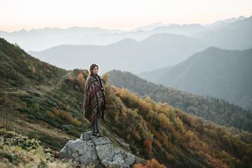 Caucasian woman standing on mountain rock overlooking valley