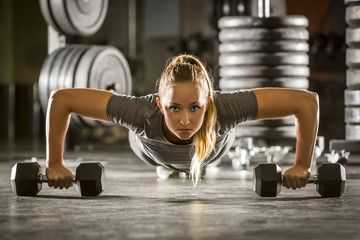 Caucasian woman doing push-up using dumbbells in gymnasium