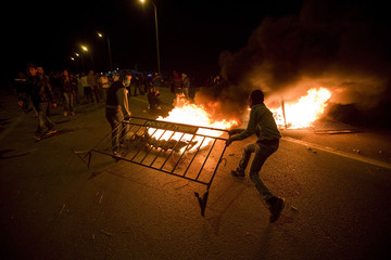 Protesters put a police barricade over burning tyres during clashes with Israeli police during a demonstration showing solidarity with Bedouin Arabs who are against a government displacement plan in Hura