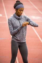 Black woman checking smart watch on track