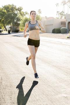Caucasian woman running in suburban street