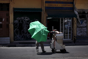 A street food vendor tries to close an umbrella against strong wind in central Athens