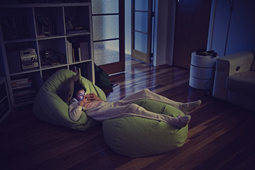 Mixed Race girl using cell phone laying on bean bags in dark