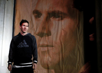 Barcelona's Messi of Argentina poses next to a picture of himself as he arrives at an event in Barcelona