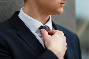Closeup of a businessman adjusting his necktie in a black suit against the background of the business center with copy space