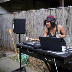 Mixed Race dj playing music in backyard