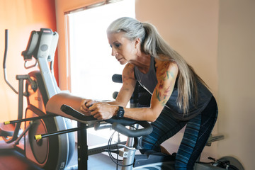 Caucasian woman riding stationary bicycle in gymnasium