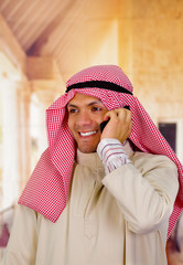 smiling cute arabian man using his cellphone