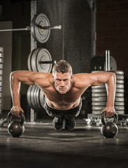 Caucasian man doing push-up using kettlebells in gymnasium