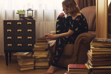 Woman sitting in armchair looking at stack of books