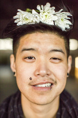 Portrait of androgynous Asian man with flowers in hair