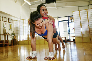 Smiling woman doing push-ups with friend laying on back
