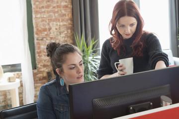Caucasian businesswomen using computer in office