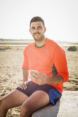 Hispanic man sitting at beach texting on cell phone