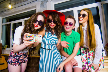 Fashionable Caucasian friends posing for cell phone selfie