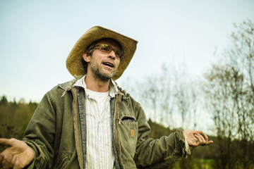 Caucasian farmer wearing cowboy hat talking and gesturing outdoors