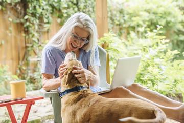 Caucasian woman using laptop petting dog on backyard patio