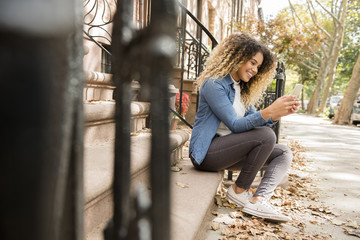 Mixed Race woman in city texting on cell phone