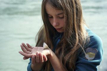Caucasian girl watching moth on hand