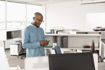 Businessman texting on smart phone in office