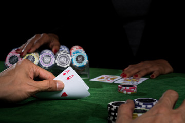 The battle in poker card gamesat a casino with chips on a green table