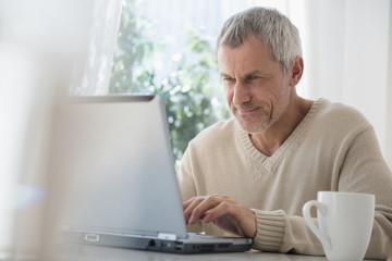Older Caucasian man using laptop