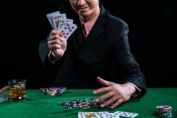 A man wearing a suit holding Hearts Suit Straight Flush on black background