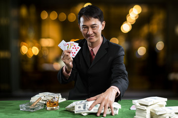 The player gather the piles of banknote when the points over rival on green table