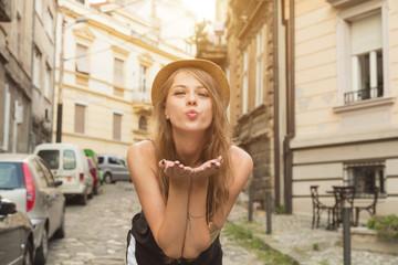Cute girl sending air kiss outdoors.