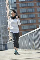 Hispanic woman running in city