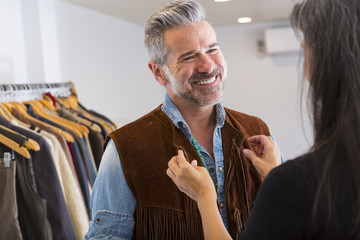 Woman helping man with fringe vest in store