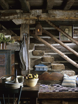 Rustic stairs descending into kitchen area in restored log home, rustic decor, 1830's settlement  bed with quilt, various antiques, pie safe, vintage mixing bowl filled with pears, Abraham Lincoln picture, bell, aprons, lantern