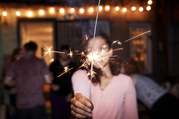 Smiling Mixed Race woman holding burning sparkler at backyard party
