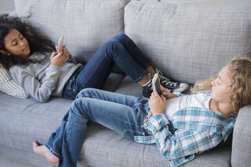 Girls laying on sofa texting on cell phones