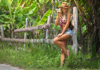 Pretty cowgirl stands by the fence,looks fresh and happy