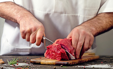 Chef cutting raw beef meat