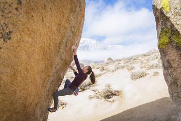 Mixed Race girl climbing rock
