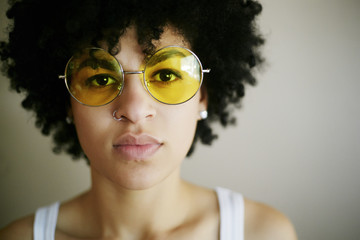 Portrait of serious Mixed Race woman wearing yellow sunglasses