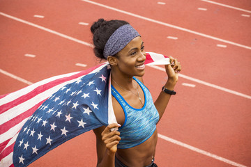 Smiling Black athlete holding American flag on track