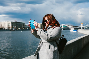 A girl takes pictures on phone landscapes