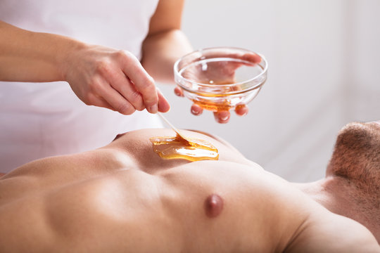 Therapist Applying Wax On Man's Body