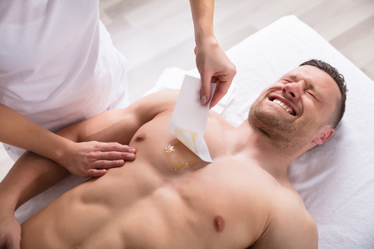 Person Waxing Man's Chest With Wax Strip