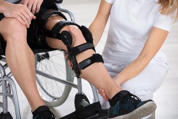 Physiotherapist Fixing Knee Braces On Man's Leg