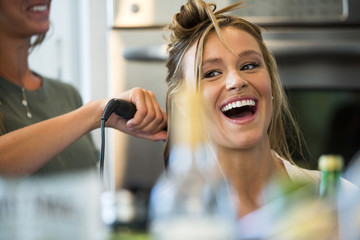 Caucasian woman smiling with hair stylist