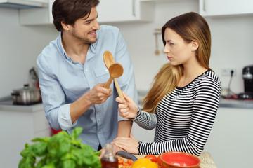 paar in der küche kreuzt die kochlöffel