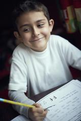 Proud Hispanic boy practicing writing alphabet