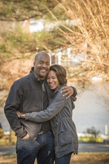 Portrait of smiling Mixed Race father and daughter hugging outdoors