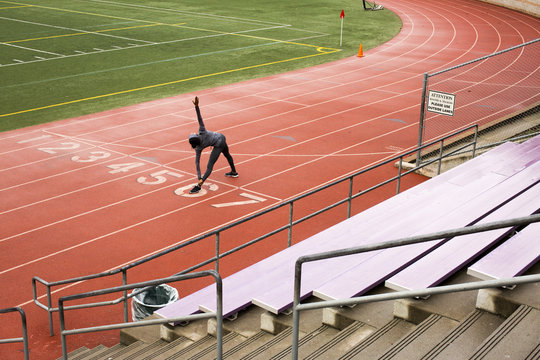 Black woman stretching on track